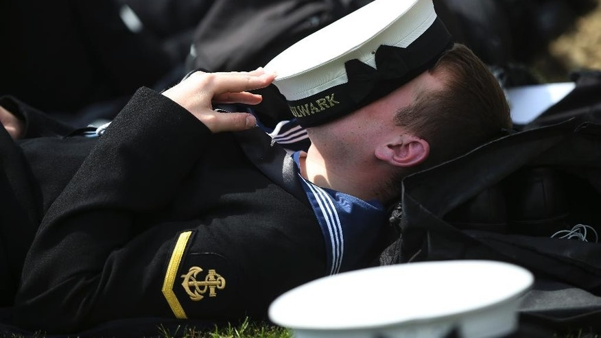 A British Royal Navy officer of the HMS Bulwark assault ship rests prior to a ceremony at the Helles Memorial in the Gallipoli peninsula, Friday, April 24, 2015. The Helles Memorial, built in 1924 and bearing more than 21,000 names serves the dual function of Commonwealth battle memorial for the whole Gallipoli campaign and place of commemoration for many of those British and Commonwealth servicemen who died there and have no known grave. As world leaders gather with the descendants of the fighters in Gallipoli, the memories of one of the most harrowing campaigns of the 20th century have come surging back to life. The doomed Allied offensive to secure a naval route from the Mediterranean to Istanbul through the Dardanelles, and take the Ottomans out of the war, resulted in over 130,000 deaths on both sides. (AP Photo/Lefteris Pitarakis)