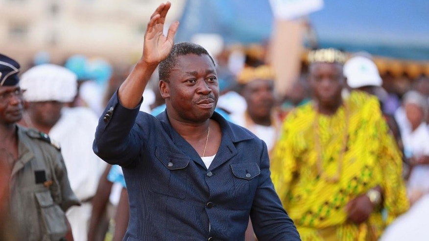 In this photo taken on Wednesday, April 22, 2015,  incumbent President Faure Gnassingbe waves to supporters during his final election rally in Lome, Togo.  Togo residents go to the polls Saturday in a vote that could see President Faure Gnassingbe remain in power for a third five-year term.  (AP Photo/Erick Kaglan)