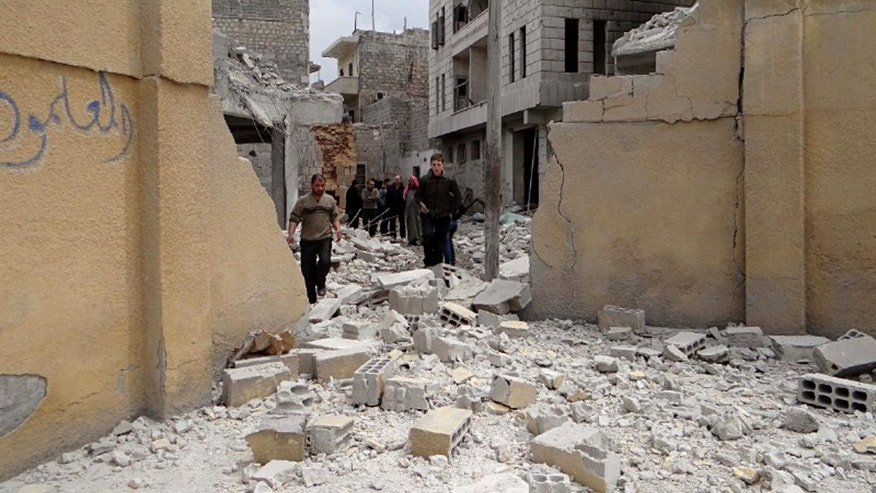 April 12, 2015 - Syrians walking at the damaged backyard of a school after a Syrian government air strike in an opposition-held neighborhood in Aleppo killed several people, including children, activists said. The UN Syria envoy  has invited the Syrian government and opposition groups for separate peace talks in Geneva next month, but no terror groups— such as the Islamic State—will be represented, a U.N. spokesman said Friday.