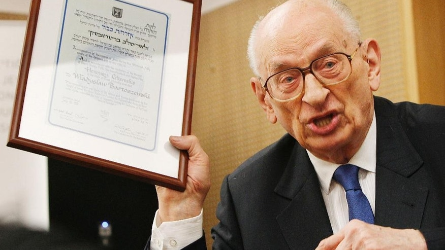 Polish man Wladyslaw Bartoszewski, who survived Auschwitz and later helped save Jews from the Holocaust, shows a copy of his honorary citizenship in Warsaw, Poland, Wednesday, Oct. 9, 2013. Bartoszewski died on Friday, April 24, 2015 at age 93. (AP Photo/Czarek Sokolowski) (AP Photo/Czarek Sokolowski)