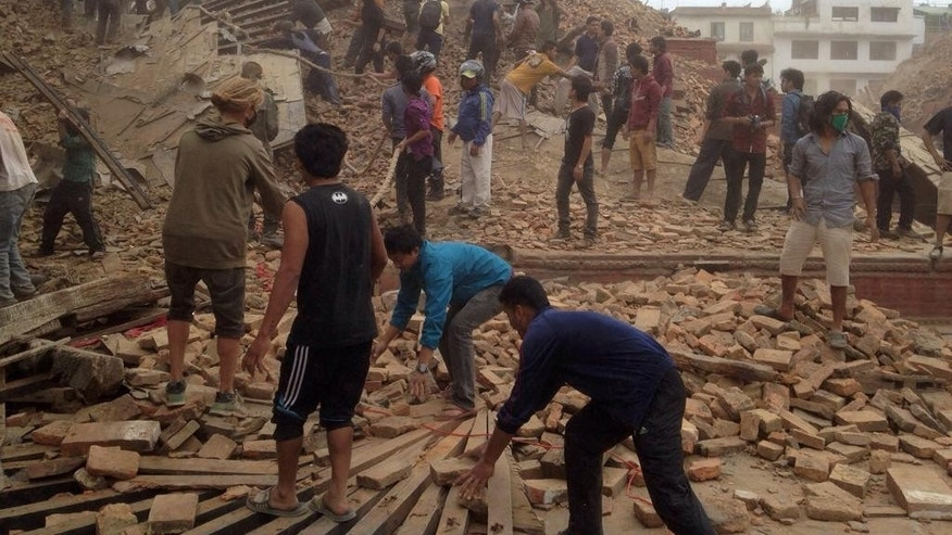 Volunteers help with rescue work at the site of a building that collapsed after an earthquake in Kathmandu, Nepal, Saturday, April 25, 2015. A strong magnitude-7.9 earthquake shook Nepal's capital and the densely populated Kathmandu Valley before noon Saturday, causing extensive damage with toppled walls and collapsed buildings, officials said. (AP Photo/ Niranjan Shrestha)