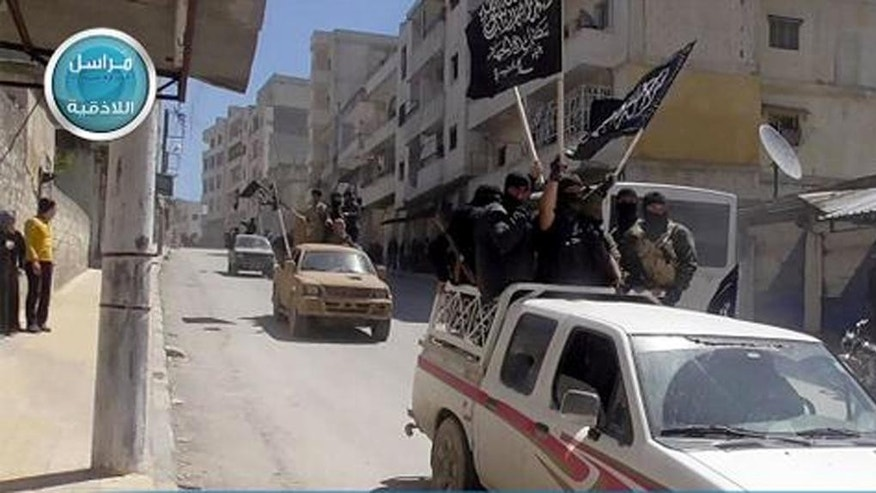 This image posted on the Twitter page of Syria's al-Qaida-linked Nusra Front on Saturday April 25, 2015, which is consistent with AP reporting, shows Nusra Front fighters standing on their vehicles and waving their group's flags as they tour the streets of Jisr al-Shughour, Idlib province, Syria. Hard-line Syrian rebel groups entered the strategic town Saturday in northwestern Syria, sending government troops fleeing after intense clashes that have seen them take nearly all of a crucial province. (Al-Nusra Front Twitter page via AP)