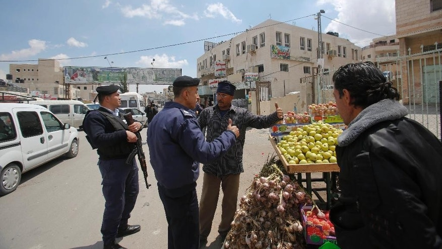 In this Monday, April 13, 2015 photo, Palestinian policemen talk to a merchant in the West Bank town of Azariyeh. After years of Israeli objections, armed Palestinian police in dark blue uniforms have taken up positions in this lawless West Bank suburb of Jerusalem, highlighting the shared interests of Israel and the Palestinian self-rule government on day-to-day issues even when political tensions run high.  (AP Photo/Nasser Shiyoukhi)