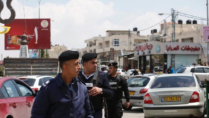 In this  Monday, April 13, 2015 photo, Palestinian police patrol in the West Bank town of Azariyeh. After years of Israeli objections, armed Palestinian police in dark blue uniforms have taken up positions in this lawless West Bank suburb of Jerusalem, highlighting the shared interests of Israel and the Palestinian self-rule government on day-to-day issues even when political tensions run high.  (AP Photo/Nasser Shiyoukhi)
