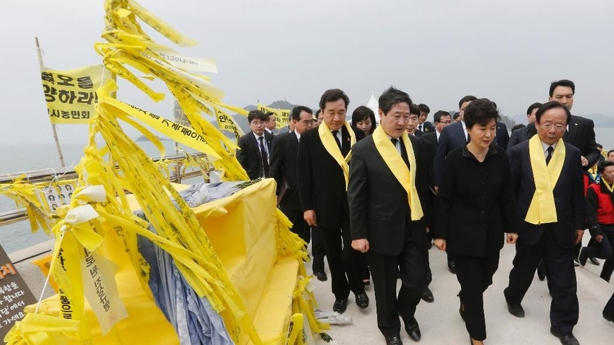 FILE - In this April 16, 2015 file photo, South Korean President Park Geun-hye, center front, passes by yellow ribbons tied with messages for victims of the sunken ferry Sewol as she arrives to offer her condolences to the bereaved relatives of the victims at a port in Jindo, South Korea. Salvaging the corroded, 6,800-ton ferry Sewol from deep beneath a channel notorious for dangerous currents will be difficult, expensive and potentially risky. It will also be one more major headache for a government already reeling from accusations that its incompetence and corruption were partly responsible for the 304 people killed when the ship sank a year ago. The government officially announced Wednesday, April 22, 2015 that it would raise the Sewol, after Park promised to do so the previous week. (Lee Jeong-ryong/Yonhap via AP, File) KOREA OUT