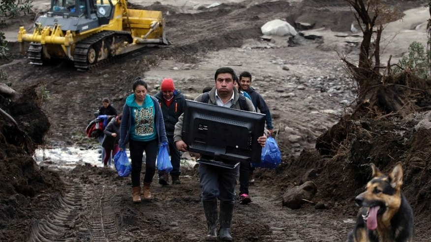 Residents evacuate with a few salvaged belongings after their home was destroyed by a volcanic mudflow, caused by the eruption of the Calbuco volcano, in an area along the Rio Blanco in Puerto Montt, Chile, Saturday, April 25, 2015. Authorities urged 2,000 people living near the volcano to evacuate Friday after potentially devastating mudflows of volcanic debris were detected in a nearby river, the result of two huge eruptions this week that sent ash across large swaths of southern South America. (AP Photo/Luis Hidalgo)