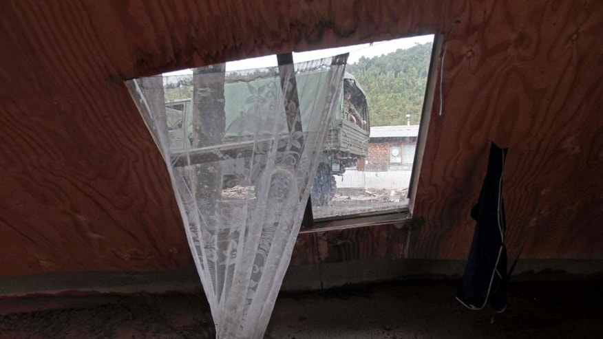 A military truck transporting aid is framed in the the window of a home destroyed by a volcanic mudflow, in an area along the Rio Blanco in Puerto Montt, Chile, Saturday, April 25, 2015. Authorities urged 2,000 people living near the volcano to evacuate Friday after potentially devastating mudflows of volcanic debris were detected in a nearby river, the result of two huge eruptions this week that sent ash across large swaths of southern South America. (AP Photo/Luis Hidalgo)