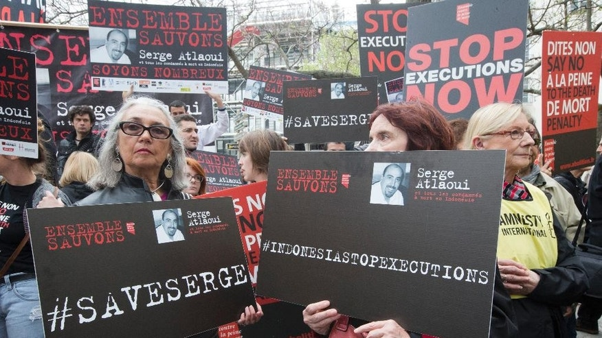 "Protesters hold placards including one reading ""Let's  save  Serge Altlaoui"" in Paris on Saturday, April 25, 2015 to show support for Serge Atlaoui, a Frenchman on death row in Indonesia, after being convicted of drug offences. Atlaoui is among nine foreign drug criminals who are facing execution by firing squad despite clemency appeals from several of their governments. (AP Photo/Jacques Brinon)"