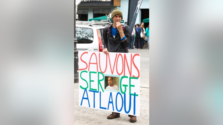 "A protester holds placard reading ""Save  Serge Altlaoui"" in Paris on Saturday, April 25, 2015, to show support for Serge Atlaoui, a Frenchman on death row in Indonesia, after being convicted of drug offences. Atlaoui is among nine foreign drug criminals who are facing execution by firing squad despite clemency appeals from several of their governments. (AP Photo/Jacques Brinon)"