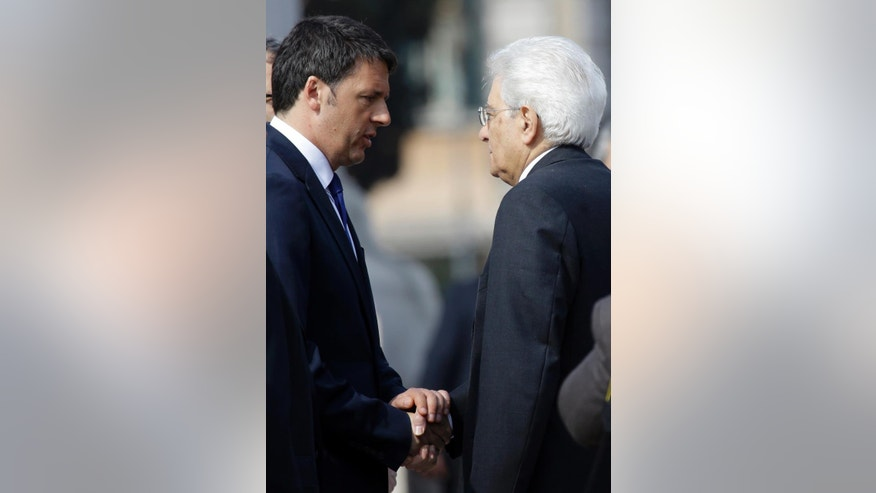 Italian President Sergio Mattarella, right, shakes hands with Italian Premier Matteo Renzi prior to a ceremony to mark Italy's Liberation day, in Rome Saturday, April 25, 2015. Italy is celebrating the 70th anniversary of a partisan uprising against the Nazis and their Fascist allies at the end of World War II. President Sergio Mattarella marked Liberation Day on Saturday by laying a wreath on the tomb of the unknown soldier in Rome. The anniversary marks the day in 1945 when the Italian resistance movement proclaimed an insurgency as the Allies were pushing German forces out of the peninsula. (AP Photo/Gregorio Borgia)