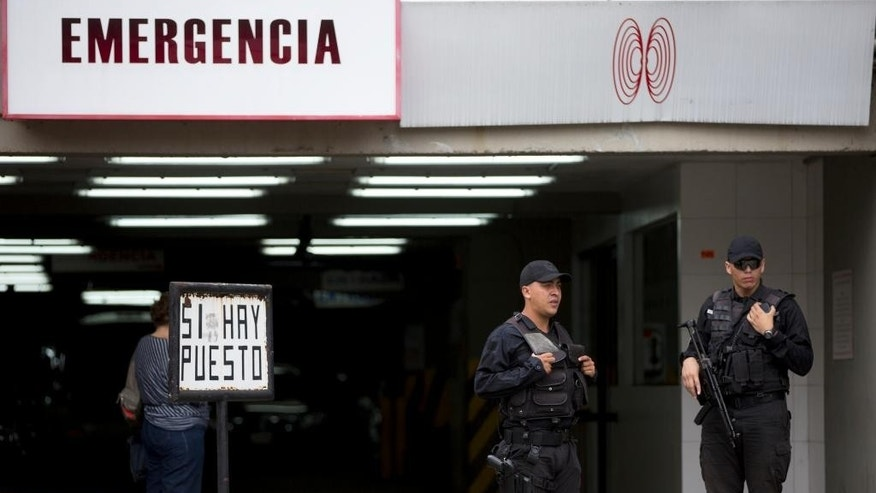 Venezuelan secret police officers stand guard outside of the San Roman Urology Hospital in Caracas, Venezuela, Saturday, April 25, 2015. The jailed mayor of Venezuela's capital has been taken from prison to the hospital where he will undergo emergency surgery for a groin hernia. Antonio Ledezma was transferred early Saturday after a court granted prosecutors' request to permit his release on medical grounds, according to his lawyer Omar Estacio. (AP Photo/Fernando Llano)