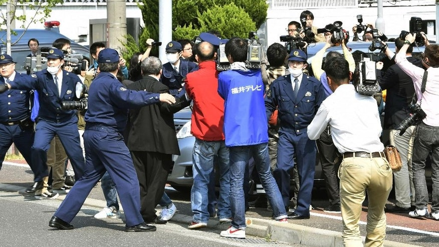 Media crowds the vehicle which carries Yasuo Yamamoto, who admitted to landing a drone on the roof of the prime minister's office, in front of Obama Police Station in Obama, Fukui prefecture, western Japan Saturday, April 25, 2015. Japanese police arrested the man, officials said Saturday. Tokyo metropolitan police said the man turned himself in late Friday in Fukui police in western Japan. (Yohei Fukai/Kyodo News via AP) JAPAN OUT, MANDATORY CREDIT