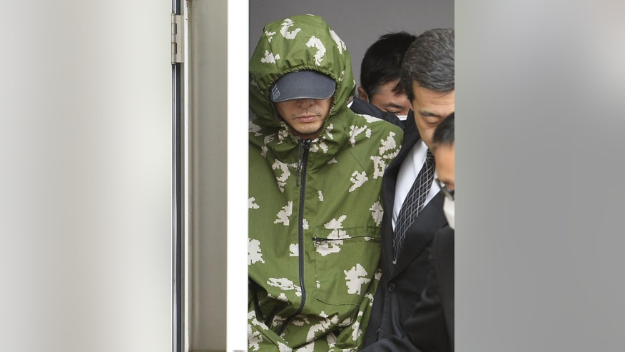 Yasuo Yamamoto, left, who admitted to landing a drone on the roof of the prime minister's office, is escorted out Obama Police Station in Obama, Fukui prefecture, western Japan Saturday, April 25, 2015. Japanese police arrested the man, officials said Saturday. Tokyo metropolitan police said the man turned himself in late Friday in Fukui police in western Japan. (Yohei Fukai/Kyodo News via AP) JAPAN OUT, MANDATORY CREDIT