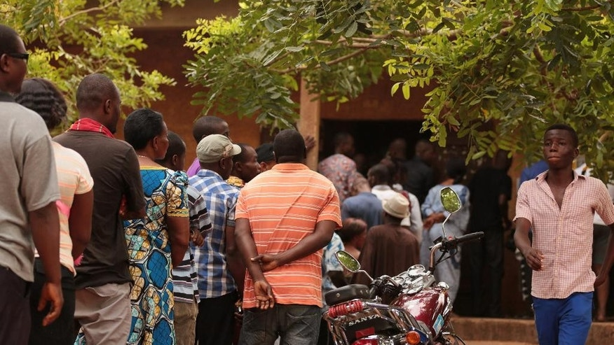 People wait in line to cast their ballot during the Togo elections, at a polling station in Lome, Togo, Saturday, April 25, 2015. Togo's president, whose family has ruled this West African nation for nearly 50 years, appealed for peace as he vied for re-election Saturday against four other candidates. (AP Photo/Erick Kaglan)