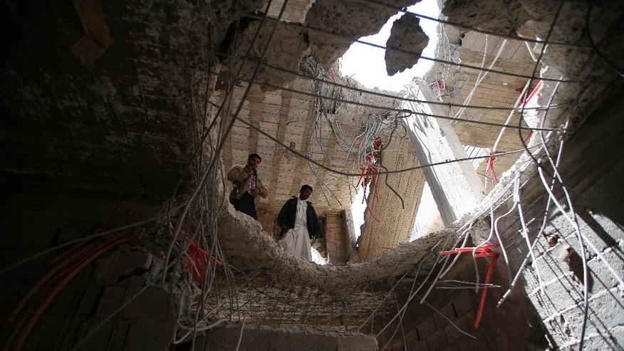 Yemeni men look through a hole in a building damaged by a recent Saudi-led airstrike which hit a site which many believe was a large weapons cache in Yemen's capital, Sanaa, Saturday, April 25, 2015.  With combatants fighting in neighborhoods and Saudi-led coalition warplanes pounding Iran-backed rebels from the sky, Yemen's war is wreaking a particularly bloody toll among civilians: more than 550 have been killed in the past month, including 115 children, the U.N. said Friday. (AP Photo/Hani Mohammed)