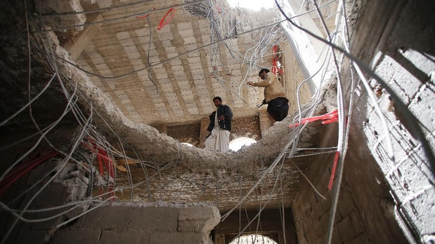 Yemeni men look through a hole in a building damaged by a recent Saudi-led airstrike which, hit a site that many believe was a large weapons cache in Yemen's capital, Sanaa, Saturday, April 25, 2015.  With combatants fighting in neighborhoods and Saudi-led coalition warplanes pounding Iran-backed rebels from the sky, Yemen's war is wreaking a particularly bloody toll among civilians: more than 550 have been killed in the past month, including 115 children, the U.N. said Friday. (AP Photo/Hani Mohammed)
