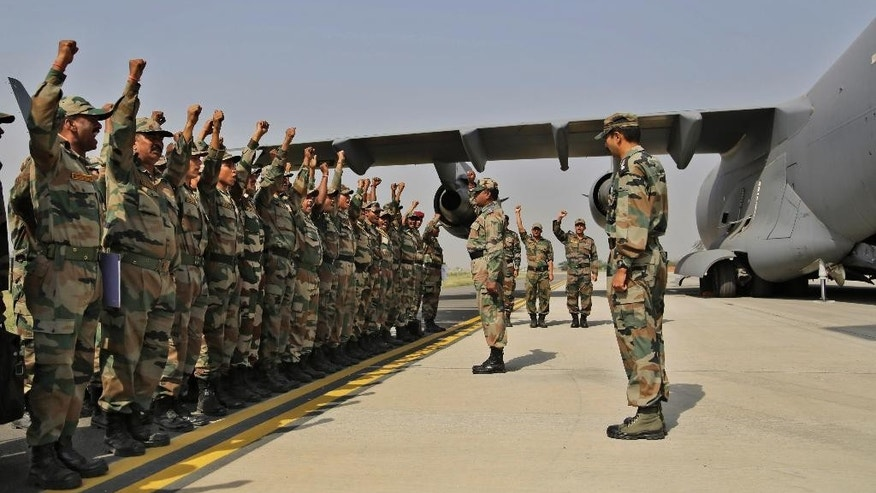 Indian soldiers on rescue mission to Nepal shout patriotic slogans before boarding an Indian Air Force aircraft near New Delhi, India, Sunday, April 26, 2015. A strong magnitude-7.9 earthquake shook Nepal's capital and the densely populated Kathmandu Valley before noon Saturday, causing extensive damage with toppled walls and collapsed buildings, officials said.(AP Photo/Altaf Qadri)
