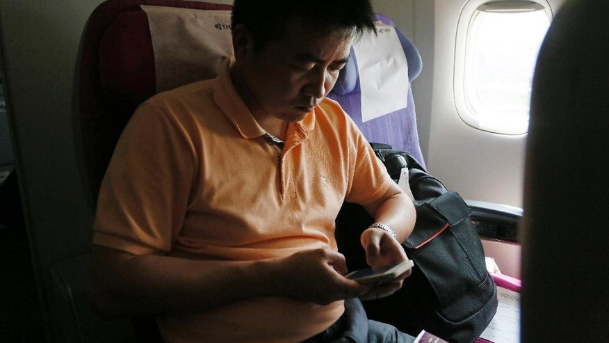 Mobile phone network engineer Sun Jun from China messages his wife while landing on the runway of Tribhuwan International Airport following an aftershock Sunday, April 26, 2015, a day after a strong earthquake in Kathmandu, Nepal. A strong magnitude 7.8 earthquake shook Nepal's capital and the densely populated Kathmandu Valley before noon Saturday, causing extensive damage with toppled walls and collapsed buildings, officials said. (AP Photo/Wally Santana)