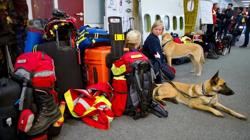 Members of a German rescue organization and their rescue dogs wait at the airport in Frankfurt, central Germany, Sunday, April 26, 2015, for their flight to earthquake-torn Nepal. International Search and Rescue Germany says a team of 52 relief workers including doctors, experts trained in searching for people buried under rubble and several dog squads will fly to Nepal. (Christoph Schmidt/dpa via AP)