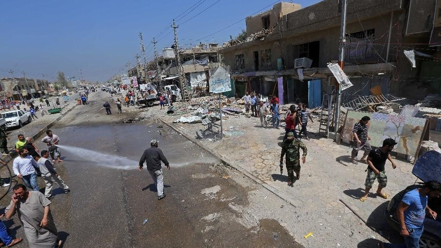 April 26, 2015: Civilians and security forces gather at the scene of a car bomb explosion in Baghdad's southwestern Amil neighborhood in Iraq.