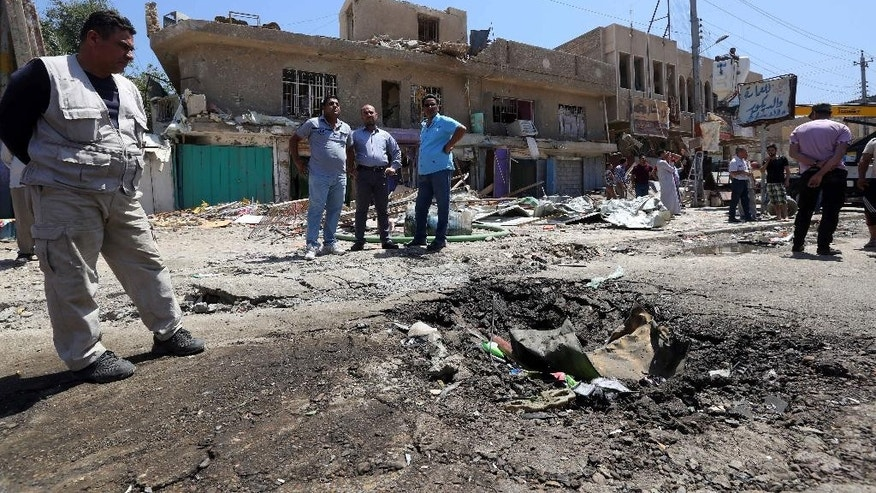 April 26, 2015: Civilians gather at the scene of a car bomb explosion in Baghdad's southwestern Amil neighborhood in Iraq.
