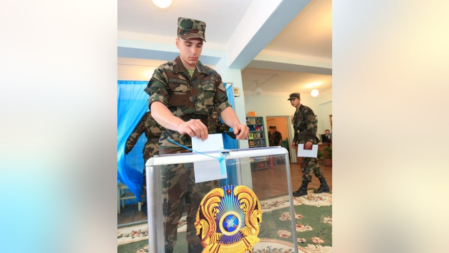 Kazakhstan's National guard soldier casts his ballot at a polling station in Almaty, Kazakhstan, Sunday, April 26, 2015. Kazakhstan is voting in a presidential election expected to overwhelmingly reconfirm the long-standing incumbent, who has ruled the former Soviet republic for more than 25 years.(AP Photo/Pavel Mikheyev)