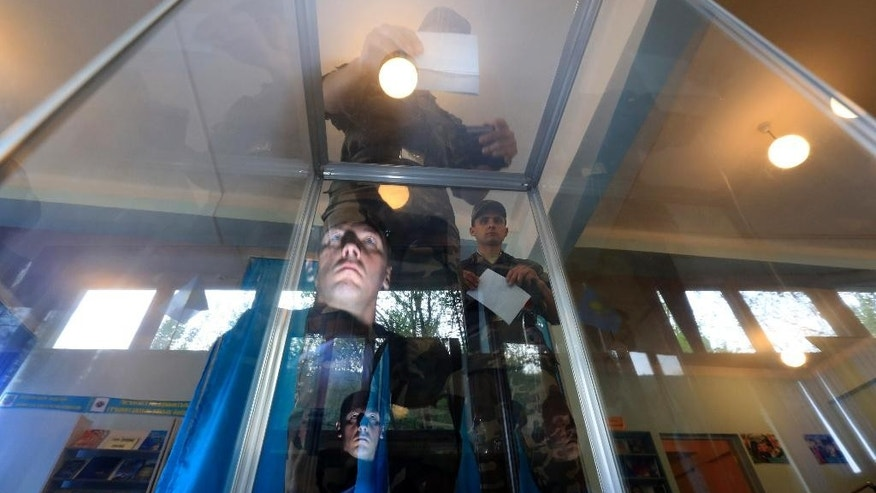 A Kazakhstan's National guard soldier casts his ballot as an other reflected in a polling box at a polling station in Almaty, Kazakhstan, Sunday, April 26, 2015. Kazakhstan is voting in a presidential election expected to overwhelmingly reconfirm the long-standing incumbent, who has ruled the former Soviet republic for more than 25 years.(AP Photo/Pavel Mikheyev)