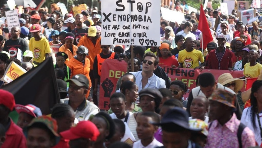 Demonstrators walk through the streets of Johannesburg Thursday, April 23, 2015 protesting  against  recent attacks on immigrants that killed seven people. The protesters walked through the center of Johannesburg passing neighborhoods that are home to many immigrants, a large number of whom come from other African countries. (AP Photo/Denis Farrell)