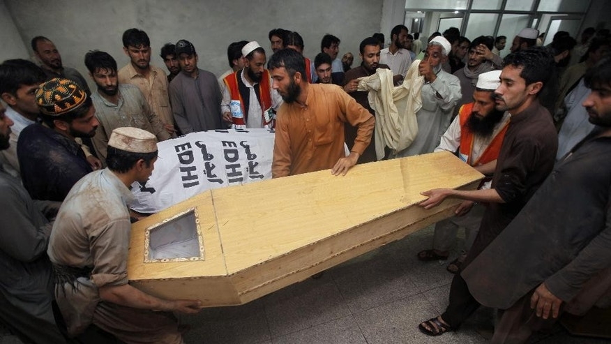 People prepare to carry a casket of the victim of heavy rains at a local hospital in Peshawar, Pakistan, Sunday, April 26, 2015. Officials in northwestern Pakistan say heavy rains have killed more than 35 people. Provincial Information Minister Mushtaq Ghani says the storm Sunday also injured hundreds of people. The storm included hailstorms and strong winds and saw buildings collapse as it uprooted trees and electric poles. (AP Photo/Muhammad Sajjad)