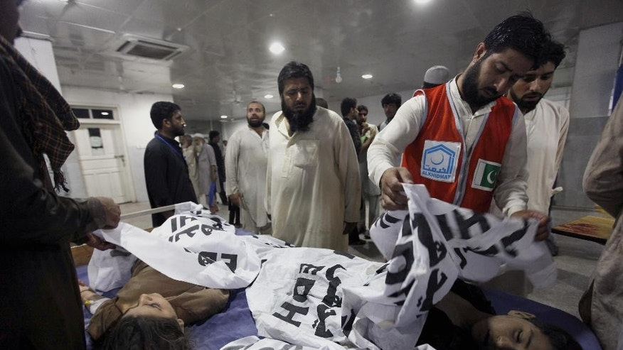 Pakistani rescue workers cover the lifeless bodies of two youngsters, who were killed in a roof collapsed caused by heavy rains, at a local hospital in Peshawar, Pakistan, Sunday, April 26, 2015. Officials in northwestern Pakistan say heavy rains have killed more than 35 people. Provincial Information Minister Mushtaq Ghani says the storm Sunday also injured hundreds of people. The storm included hailstorms and strong winds and saw buildings collapse as it uprooted trees and electric poles. (AP Photo/Muhammad Sajjad)