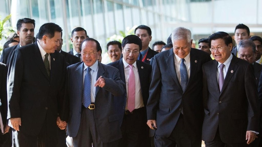 Foreign ministers of the Association of Southeast Asian Nations (ASEAN), from left to right, Thailand's Tanasak Patimapragorn, Cambodia's Hor Namhong, Vietnam's Pham Binh Minh, Philippines' Foreign Secretary Albert del Rosario, Laos' Thongloun Sisoulith arrive for the 26th ASEAN Summit Foreign Ministers Meeting at Kuala Lumpur Convention Center in Kuala Lumpur, Malaysia on Sunday, April 26, 2015. (AP Photo/Joshua Paul)