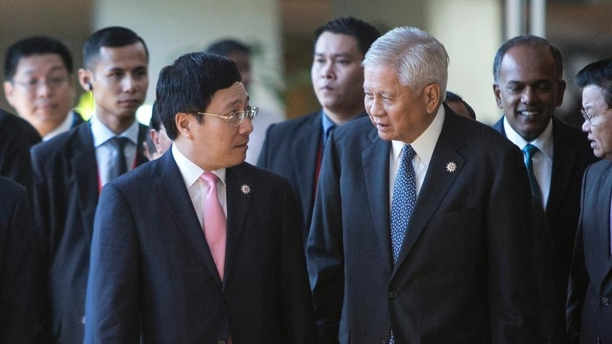 Vietnam's Foreign Minister Pham Binh Minh, left, chats with Philippines' Foreign Secretary Albert del Rosario as they arrive for the 26th ASEAN Summit Foreign Ministers Meeting at Kuala Lumpur Convention Center in Kuala Lumpur, Malaysia on Sunday, April 26, 2015. (AP Photo/Joshua Paul)