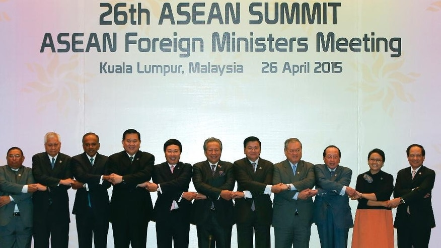 Ministers of the Association of Southeast Asian Nations, or ASEAN countries, from left to right, Myanmar's Foreign Minister Wunna Maung Lwin, Philippines' Foreign Secretary Albert del Rosario, Singapore's Foreign Minister K Shanmugam, Thailand's Foreign Minister Tanasak Patimapragorn, Vietnam's Foreign Minister Pham Binh Minh, Malaysia's Foreign Minister Anifah Aman,  Laos's Foreign Minister Thongloun Sisoulith, Brunei's Foreign Minister Lim Jock Seng, Cambodia's Foreign Minister Hor Namhong, Indonesia's Foreign Minister Retno Marsudi and ASEAN Secretary-General Le Luong Minh join their arms as they pose for a group photo during the 26th ASEAN Summit Foreign Ministers Meeting at Kuala Lumpur Convention Centre in Kuala Lumpur, Malaysia on Sunday, April 26, 2015. (AP Photo/Joshua Paul)
