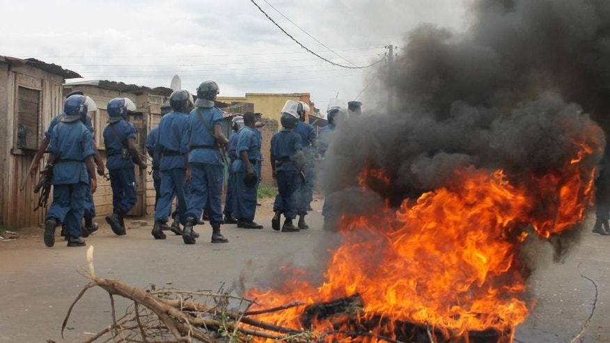 Burundian riot police march past a burning tyre roadblock following clashes with opposition protesters in a street in the capital Bujumbura, Burundi Sunday, April 26, 2015. Hundreds of people in Burundi protested in the capital Sunday after the country's ruling party nominated President Pierre Nkurunziza to run for a third term. (AP Photo)
