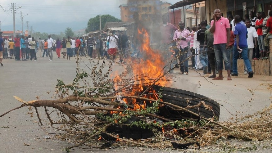 Residents gather around a burning tyre roadblock following clashes between police and opposition protesters in a street in the capital Bujumbura, Burundi Sunday, April 26, 2015. Hundreds of people in Burundi protested in the capital Sunday after the country's ruling party nominated President Pierre Nkurunziza to run for a third term. (AP Photo)