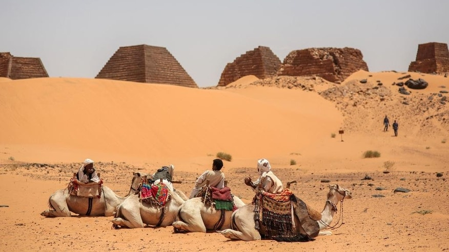 In this Thursday, April 16, 2015 photo, tour guides wait for tourists to offer them camel rides at the historic Meroe pyramids in al-Bagrawiya, 200 kilometers (125 miles) north of Khartoum, Sudan. The pyramids at Meroe are deserted despite being a UNESCO World Heritage site like those at Giza in Egypt.  (AP Photo/Mosa'ab Elshamy)