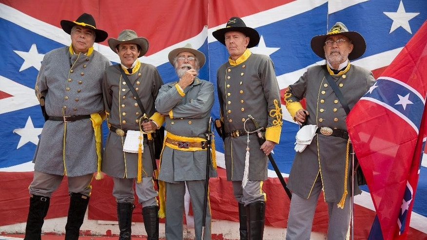 """Descendants of American Southerners wearing Confederate-era uniforms pose for pictures as they attend a party to celebrate the 150th anniversary of the end of the American Civil War in Santa Barbara d'Oeste, Brazil, Sunday, April 26, 2015. For many of the residents of Santa Barbara d'Oeste and neighboring Americana, in Brazil's southeastern Sao Paulo state, having Confederate ancestry is a point of pride and is celebrated in high style at the annual """"Festa dos Confederados,"""" or """"Confederates Party"""" in Portuguese. (AP Photo/Andre Penner)"""