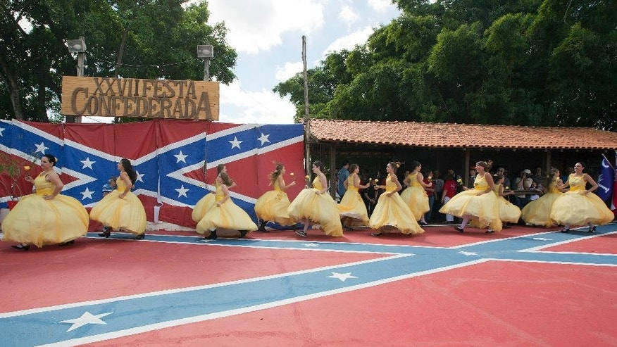 """Descendants of American Southerners Wearing Confederate-era dresses dance during a party to celebrate the 150th anniversary of the end of the American Civil War in Santa Barbara d'Oeste, Brazil, Sunday, April 26, 2015. Amid food and beer stands bedecked with red-white-and-blue ribbons, extended families tucked into diet-busting barbecue and hamburger lunches as """"Dixie"""" played on a loop. Teenage girls pulled hoop skirts over their cut-off short-shorts and wiggled into bustier tops, taking to the stage painted with a giant Confederate flag on the arms of young men in grey and yellow uniforms. (AP Photo/Andre Penner)"""