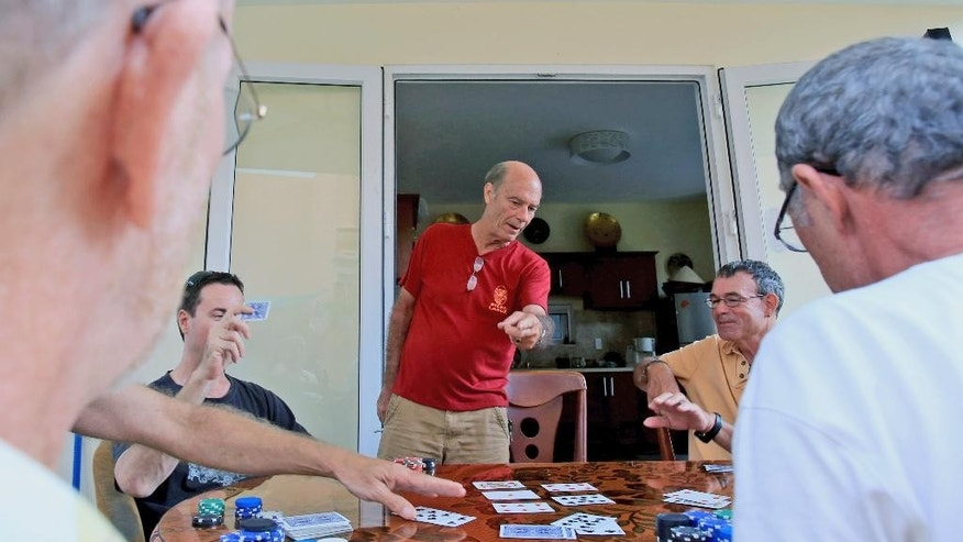 In this April 11, 2015, photo, Bill Ervin, a former U.S. Marine from Colorado who now runs a travel company with his Vietnamese wife, reacts while playing poker with fellow Vietnam war veterans at his house in Danang, Vietnam. The presence of American war veterans in today's Vietnam - and the warm welcome they usually receive - is yet another sign of how much the U.S.-Vietnamese relationship has evolved since the countries normalized relations in 1995. (AP Photo/Hau Dinh)