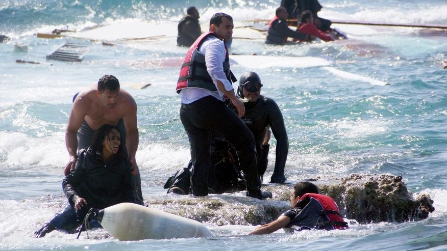 FILE - In this Monday, April 20, 2015 file photo, Greek army Sgt. Antonis Deligiorgis, standing at left, rescues migrant Wegasi Nebiat from Eritrea, front left, from the Aegean sea, on the island of Rhodes, Greece. Deligiorgis was awarded the Cross of Excellency by Defense Minister Panos Kammenos at an Athens ceremony Monday, April 27, 2015 for his role in rescuing passengers from a ship carrying migrants from Turkey that sank after crashing into rocks a week ago. (Argiris Mantikos/Eurokinissi via AP, File) GREECE OUT