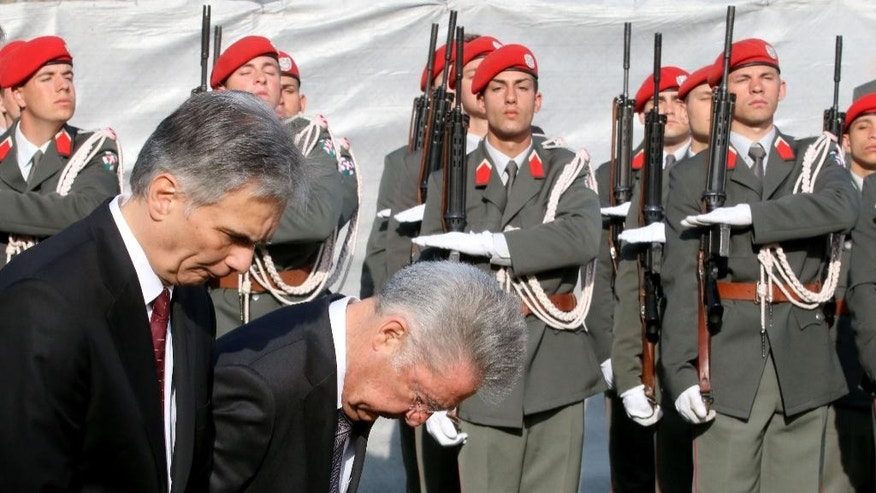 Austrian Chancellor Werner Faymann and Austrian President Heinz Fischer, from left, take a bow in front of the National Foundation Memorial in Vienna, Austria, Monday, April 27, 2015. The Second Republic  of Austria was established 70 years ago. (AP Photo/Ronald Zak)