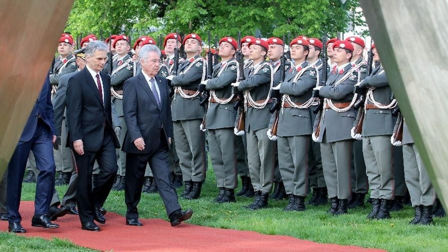 Austrian Chancellor Werner Faymann and Austrian President Heinz Fischer, from left,  review the honor guard in front of the National Foundation Memorial in Vienna, Austria, Monday, April 27, 2015. The Second Republic  of Austria was established 70 years ago. (AP Photo/Ronald Zak)