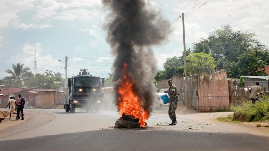 A Burundian army soldier pours water on a burning-tyre roadblock erected by opposition protesters in the capital Bujumbura, Burundi Monday, April 27, 2015. Street protests continued Monday in Burundi as anger mounts over the ruling party's decision on Saturday to nominate President Pierre Nkurunziza for a third term. (AP Photo/Eloge Willy Kaneza)