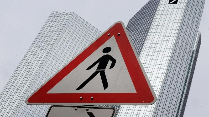 "A traffic sign stands near the headquarters of the Deutsche Bank in Frankfurt, Germany, Saturday, April 25, 2015.  Deutsche Bank AG says it plans to ""deconsolidate"" its Postbank retail banking unit, in which it has held a majority since 2010. (AP Photo/Michael Probst)"