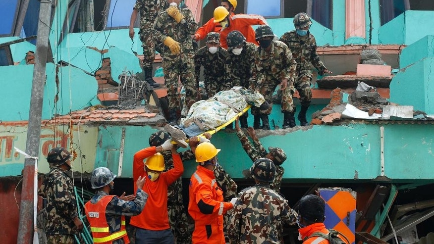In this April 27, 2015 photo, Nepalese and Indian rescue teams remove a body from the collapsed Sitapyla church in Kathmandu, Nepal. A strong earthquake shook Nepal's capital and the densely populated Kathmandu Valley on Saturday. The catastrophe has overwhelmed Nepal's government, with the challenge expected to worsen as the death toll climbs as rescuers reach vulnerable mountain villages that were hit hard. (AP Photo/Wally Santana)