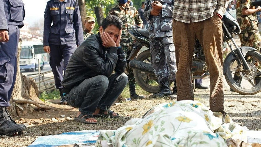 In this April 27, 2015 photo, a man grieves over the body of his relative recovered at the collapsed Sitapyla church in Kathmandu, Nepal. A strong earthquake shook Nepal's capital and the densely populated Kathmandu Valley on Saturday. The catastrophe has overwhelmed Nepal's government, with the challenge expected to worsen as the death toll climbs as rescuers reach vulnerable mountain villages that were hit hard. (AP Photo/Wally Santana)