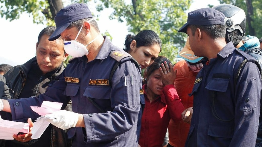 In this April 27, 2015 photo, as police check records, a woman reacts while identifying the body of a relative removed from the collapsed Sitapyla church in Kathmandu, Nepal. A strong earthquake shook Nepal's capital and the densely populated Kathmandu Valley on Saturday. The catastrophe has overwhelmed Nepal's government, with the challenge expected to worsen as the death toll climbs as rescuers reach vulnerable mountain villages that were hit hard. (AP Photo/Wally Santana)