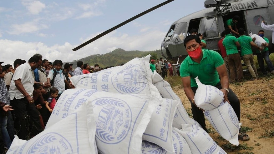 Nepalese volunteers unload relief material brought in an Indian air force helicopter for victims of Saturday's earthquake at Trishuli Bazar in Nepal, Monday, April 27, 2015. Wedged between the two rising Asian powers of China and India, landlocked Nepal saw rescuers and offers of help pour from both sides within hours of its massive earthquake. (AP Photo/Altaf Qadri)