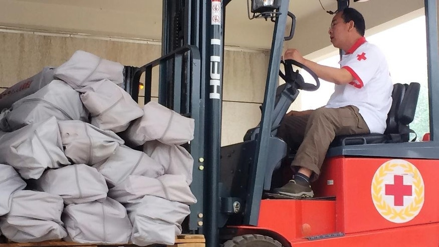 A Chinese Red Cross worker operates a forklift carrying tents at a warehouse in Beijing Monday, April 27, 2015. Wedged between the two rising Asian powers of China and India, landlocked Nepal saw rescuers and offers of help pour from both sides within hours of its massive earthquake. The Chinese Red Cross shipped 2,000 tents by air to Kathmandu on Monday as part of its relief efforts for the earthquake in Nepal, which the agency said would be enough to shelter 10,000 to 12,000 people. (AP Photo/Isolda Morillo)