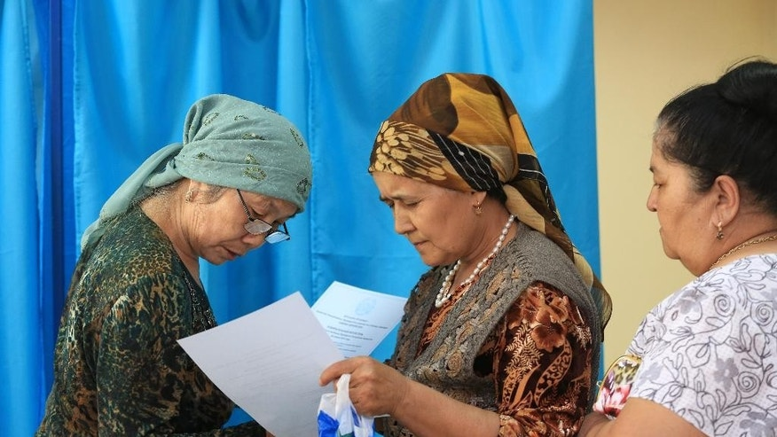 Kazakh women consulate each other after filling in their ballots before voting as a member of an election commission, right, points her the direction to a ballot box at a polling station outside Almaty, Kazakhstan, Sunday, April 26, 2015. Voters in Kazakhstan turned out in abundance at polling stations Sunday for a presidential election guaranteed to overwhelmingly reconfirm the 74-year-old incumbent, who has ruled over the former Soviet republic for more than 25 years. (AP Photo/Pavel Mikheyev)
